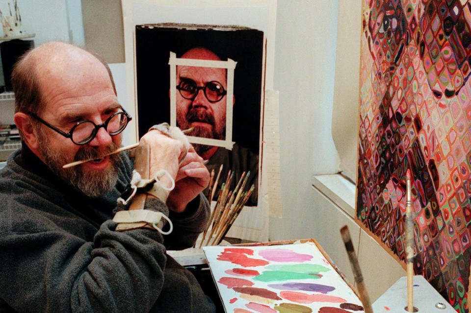 FILE - In this Jan. 3, 1996, file photo, Chuck Close, 55, using a hand brace to hold his paint brush, adjusts the brush with his teeth while working in his New York studio. Since suffering a partial paralysis in 1988 due to a spinal artery collapse, Close does not have the strength to grip the brush. Close who is best known for his monumental grid portraits and photo-based paintings of family and famous friends, has died on Thursday, Aug. 19, 2021, at age 81. (AP Photo/Mark Lennihan, File)