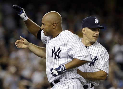 New York Yankees manager Joe Girardi, right, congratulates Vernon Wells after a baseball game against the Baltimore Orioles, Friday, July 5, 2013, in New York. The Yankees won the game 3-2 with Wells' RBI-single. (AP Photo/Frank Franklin II)