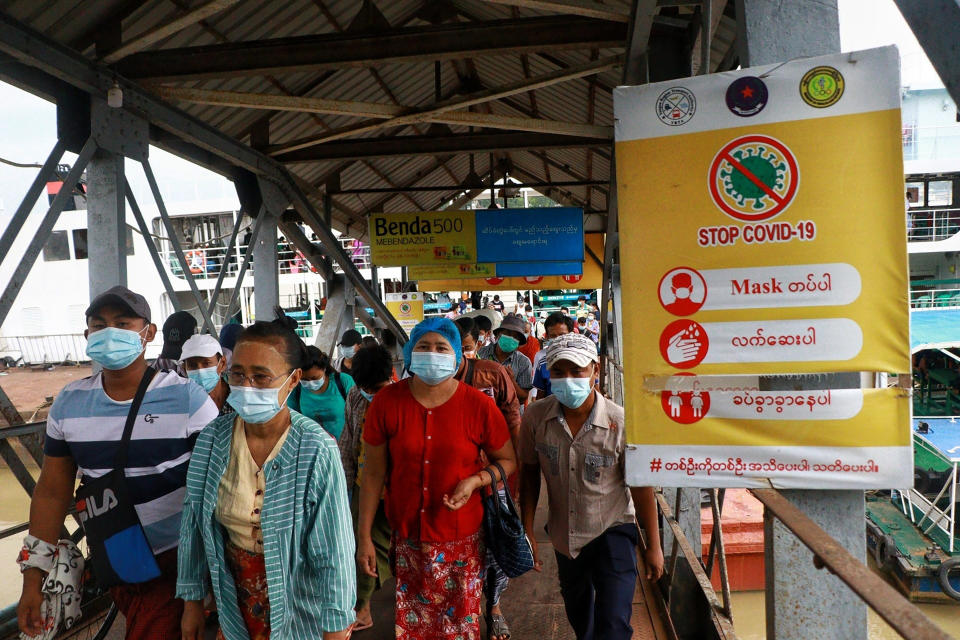"""FILE - In this July 27, 2021, file photo, ferry passengers wearing face masks to help curb the spread of the coronavirus walk past a """"Stop COVID-19"""" poster at the Pansodan jetty in Yangon, Myanmar. With coronavirus deaths rising in Myanmar, there are growing allegations from residents and human rights activists that the military government, which seized control in February, is using the pandemic to consolidate power and crush opposition. (AP Photo, File)"""