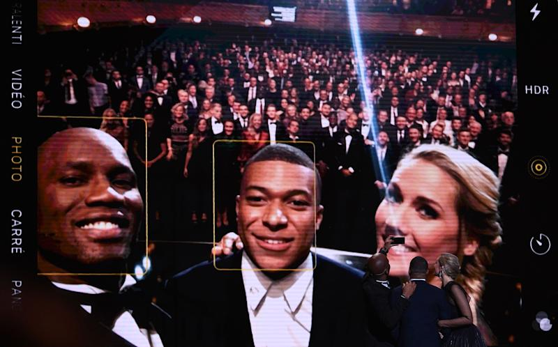 Didier Drogba (left) took a selfie with Kylian Mbappe (center) that was 10 years in the making. (Photo by FRANCK FIFE / AFP) (Photo by FRANCK FIFE/AFP via Getty Images)