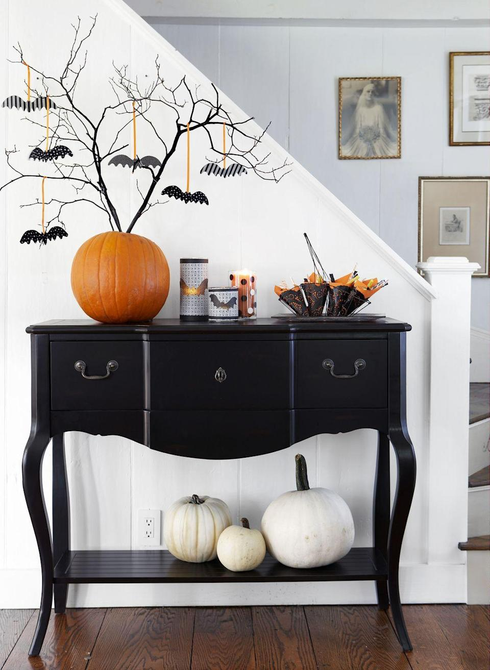 """<p>Perk up the foyer with a bevy of fluttering bats. Simply stick backyard branches into a plain pumpkin and hang a few spooky ornaments. </p><p><em><a href=""""https://www.goodhousekeeping.com/holidays/halloween-ideas/g421/halloween-decorating-ideas-1007/"""" rel=""""nofollow noopener"""" target=""""_blank"""" data-ylk=""""slk:Get the tutorial »"""" class=""""link rapid-noclick-resp"""">Get the tutorial »</a></em></p>"""