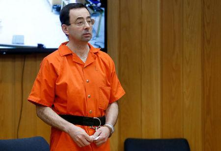 FILE PHOTO: Larry Nassar, a former team USA Gymnastics doctor who pleaded guilty in November 2017 to sexual assault charges, stands in court during his sentencing hearing in the Eaton County Court in Charlotte, Michigan, U.S., February 5, 2018. REUTERS/Rebecca Cook