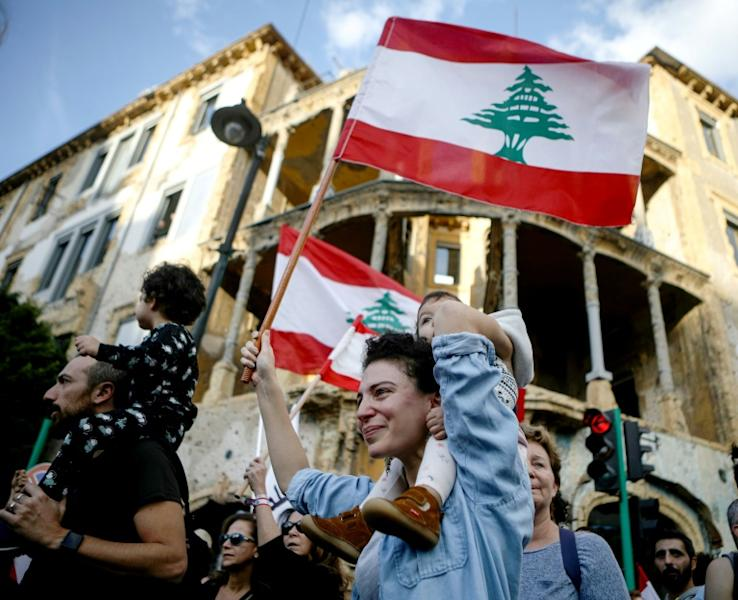 Lebanese anti-government protesters wave the national flag in a march in Beirut (AFP Photo/Patrick BAZ)