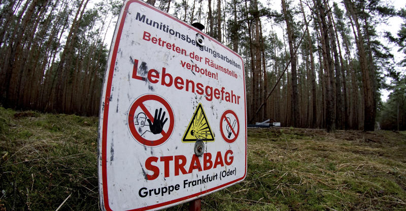 In this Wednesday, Jan. 8, 2020 photo a sign warns visitors of World War II munition at the site of the planned new Tesla Gigafactory in Gruenheide near Berlin, Germany. Tesla CEO Elon Musk said during an awards ceremony in Berlin in November 2019 that 'we have decided to put the Tesla Gigafactory Europe in the Berlin area.' The company will also set up an engineering and design center in Berlin, Musk said. He wrote on Twitter that the new plant 'will build batteries, powertrains & vehicles, starting with Model Y.' (AP Photo/Michael Sohn)