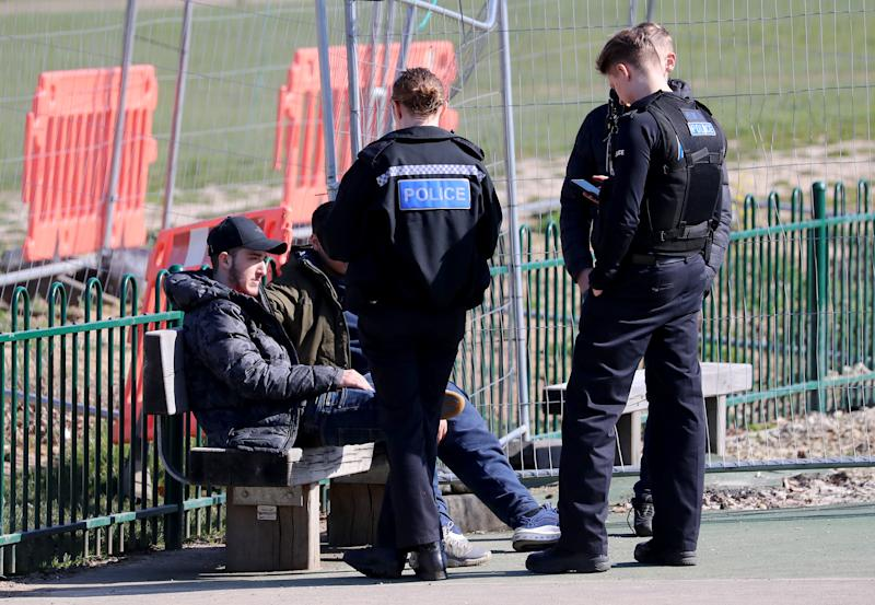 A group of young men are spoken to by Kent Police officers before being dispersed from a children's play area in Mote Park, Maidstone, the day after Prime Minister Boris Johnson put the UK in lockdown to help curb the spread of the coronavirus.