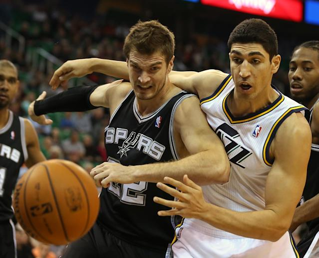 San Antonio Spurs' Tiago Splitter, left, and Utah Jazz's Enes Kanter fight for the ball during the first half of an NBA basketball game in Salt Lake City, Friday, Nov. 15, 2013. (AP photo/George Frey)