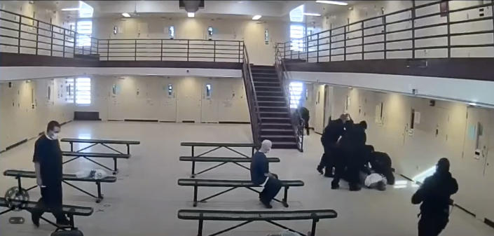 In this image made from video provided by the Ohio Department of Rehabilitation and Correction, prison guards escort Michael McDaniel, 55, in white shirt on the ground, to the medical facility at the Correctional Reception Center in Orient, Ohio. Ohio's correctional agency has terminated seven employees after officials say prison guards used excessive and unjustified force against a Black inmate before he died in custody in February. The Ohio Department of Rehabilitation & Correction sent a notice of removal to five corrections officers, a supervisor and a licensed nurse following an investigation into the in-custody death of 55-year-old Michael McDaniel. (Ohio Department of Rehabilitation and Correction via AP)
