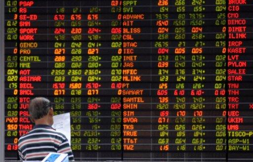 A Thai investor reads a document in front of an electronic shares price display at the stock exchange in Bangkok
