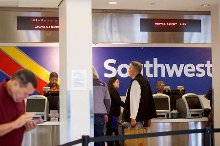 FILE PHOTO: Southwest Arlines employees check in travelers at the Philadelphia International Airport