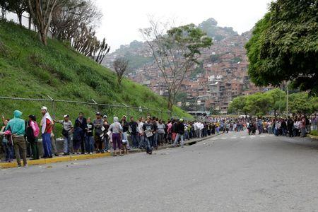 People queue in a street outside a supermarket to try to buy basic food items in Caracas, Venezuela, May 15, 2016. REUTERS/Marco Bello