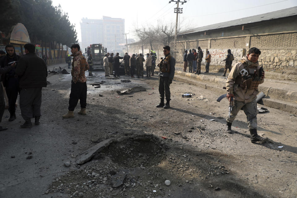 Afghan security officers inspect the site of a bombing attack in Kabul, Afghanistan, Sunday, Jan. 10, 2021. A roadside bomb exploded in Afghanistan's capital Sunday, killing at least a few people in a vehicle, the latest attack to take place even as government negotiators are in Qatar to resume peace talks with the Taliban. (AP Photo/Rahmat Gul)