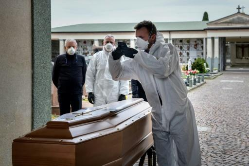 A pallbearer takes a picture of a coffin for the relatives of someone who has died, at a cemetery in the Italian province of Bergamo