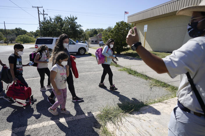 A member of a humanitarian group, right, greets migrants after they were released from U.S. Customs and Border Protection custody, Friday, Sept. 24, 2021, in Del Rio, Texas. (AP Photo/Julio Cortez)