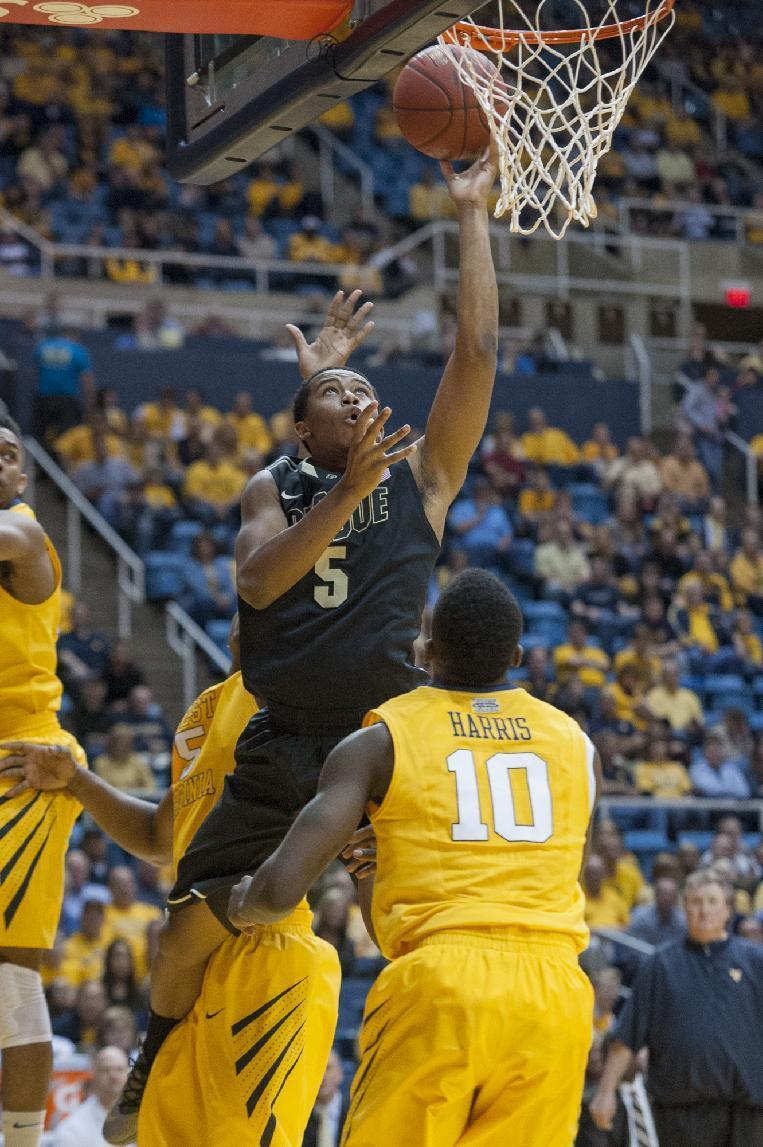 Purdue's Basil Smotherman, top, drives by West Virginia defenders during the first half of an NCAA college basketball game on Sunday, Dec. 22, 2013, in Morgantown, W.Va. (AP Photo/Andrew Ferguson)