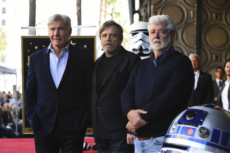 "Mark Hamill, center, poses with fellow ""Star Wars"" cast member Harrison Ford, left, and creator George Lucas as Hamill is honored with a star on the Hollywood Walk of Fame on Thursday, March 8, 2018 in Los Angeles. (Photo by Jordan Strauss/Invision/AP)"