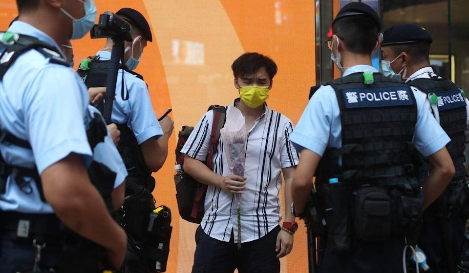 Police question a man carrying flowers near the site of the stabbing in Causeway Bay. Photo: Xiaomei Chen