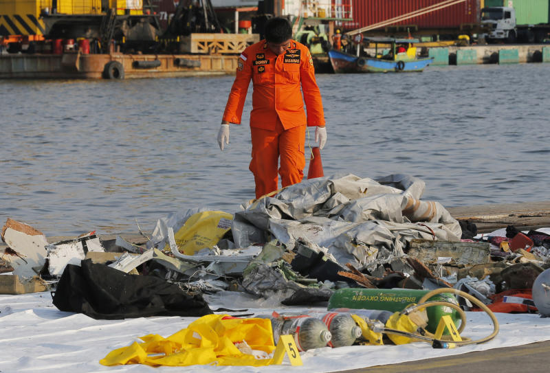 A member of Indonesian Search and Rescue Agency (BASARNAS) inspects debris recovered from near waters where a Lion Air passenger jet is suspected to crash off, at Tanjung Priok Port in Jakarta, Indonesia Monday, Oct. 29, 2018. A Lion Air flight crashed into the sea just minutes after taking off from Indonesia's capital on Monday in a blow to the country's aviation safety record after the lifting of bans on its airlines by the European Union and U.S. (AP Photo/Tatan Syuflana)