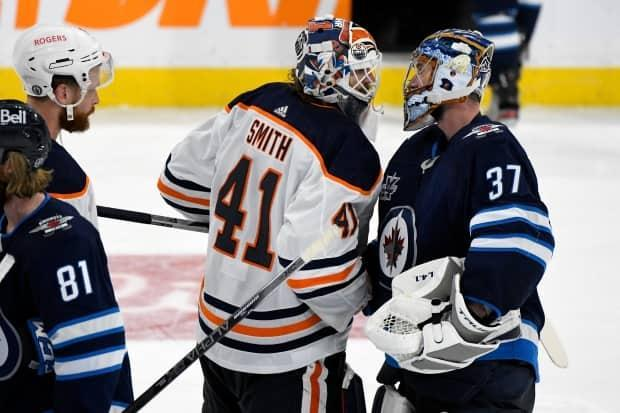 Jets goaltender Connor Hellebuyck, right, shakes hands with Oilers goaltender Mike Smith after Winnipeg eliminated Edmonton on Monday.