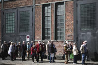 People line up in front of the vaccination center at the Arena Treptow in Berlin, Germany, Wednesday, March 31, 2021. This vaccination center in the German capital's Treptow district has used only the Pfizer vaccine since it was opened. German health officials agreed on Tuesday to restrict the use of AstraZeneca's vaccine in people under 60. (AP Photo/Markus Schreiber)