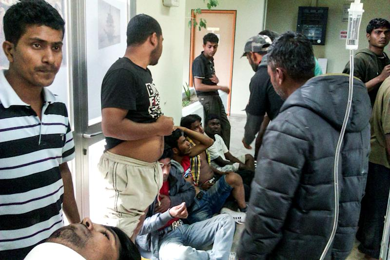In this image taken on Wednesday, April 17, 2013, unidentified migrant workers receive first aid at the Medical Center of Varda, in Greece. At least 20 migrant strawberry pickers, most of them from Bangladesh, were shot and wounded in southern Greece on Wednesday, in a pay dispute after a foreman opened fire on them with a shotgun, police said. The incident occurred near the village of Manolada about 260 kilometers (160 miles) west of Athens. (AP Photo/EUROKINISSI) GREECE OUT