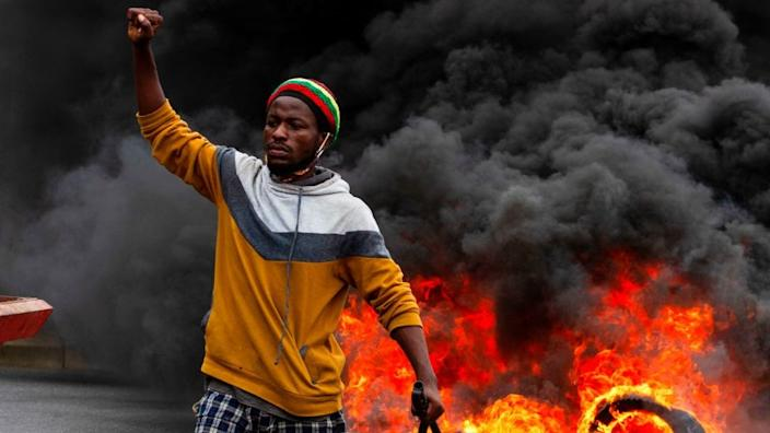 A protester gestures while standing in front of burning tyres during a anti-government demonstration in Luanda on October 24, 2020.