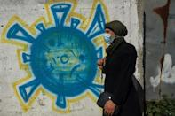 Tahani al-Rifi walks past a coronavirus-inspired mural in Gaza; one of some 7,000 Gazans who are currently diagnosed with cancer - but only about 100 of them are expecting permission to cross into Israel to access treatment