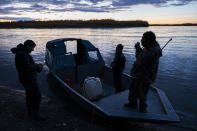 Hunters in the Stevens' family talk on shore before moving inland to camp for the night on Tuesday, Sept. 14, 2021, near Stevens Village, Alaska. For the first time in memory, both king and chum salmon have dwindled to almost nothing and the state has banned salmon fishing on the Yukon. The remote communities that dot the river and live off its bounty are desperate and doubling down on moose and caribou hunts in the waning days of fall. (AP Photo/Nathan Howard)