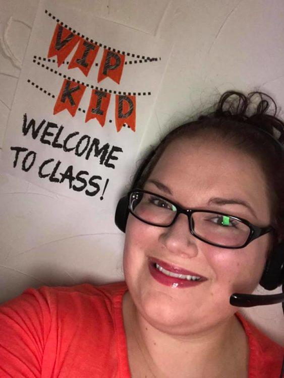 woman with headset and welcome to class sign