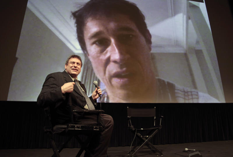 """This Sept. 13, 2012 photo shows Richard Pena, director of the New York Film Festival (NYFF), hosting a live interview via Skype video with film director Bertrand Bonello, following a press screening of his festival entry """"Ingrid Caven: Voice and Music"""" in New York. Pena will step down as head of the Film Society of Lincoln Center and the NYFF after this year's 50th Anniversary of NYFF presentation, a post he has held for 25 years. (AP Photo/Bebeto Matthews)"""