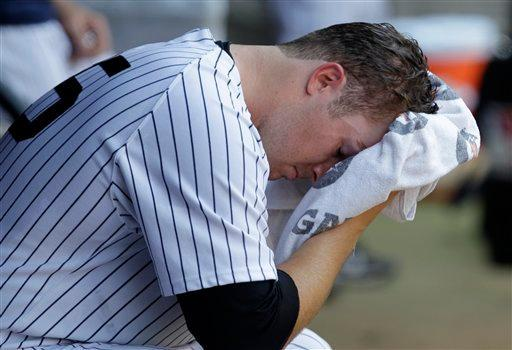 New York Yankees starting pitcher Phil Hughes wipes his face in the dugout after manager Joe Girard removed him from the mound during the fifth inning of the Yankees baseball game against the Atlanta Braves at Yankee Stadium in New York, Wednesday, June 20, 2012. (AP Photo/Kathy Willens)