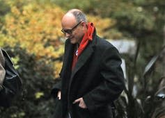 A bald man in a black coat and red scarf walks with his head down.
