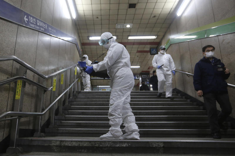 "Workers wearing protective gears spray disinfectant as a precaution against the coronavirus at a subway station in Seoul, South Korea, Friday, Feb. 21, 2020. South Korea on Friday declared a ""special management zone"" around a southeastern city where a surging viral outbreak, largely linked to a church in Daegu, threatens to overwhelm the region's health system. (AP Photo/Ahn Young-joon)"