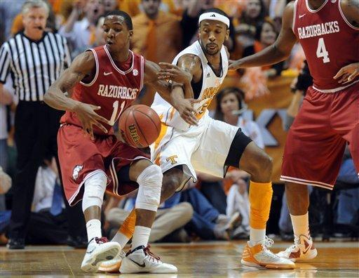 Tennessee guard Cameron Tatum (23) swipes the ball away from Arkansas guard BJ Young (11) during the first half of an NCAA college basketball game at Thompson-Boling Arena in Knoxville, Tenn., Wednesday, Feb. 15, 2012. Tennessee won 77-58 over Arkansas. (AP Photo/Knoxville News Sentinel, Adam Brimer)