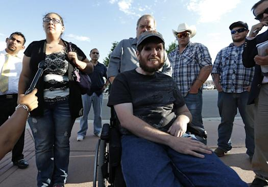 Caleb Medley, center, who was shot in the face in the 2012 Aurora movie theater massacre, sits in a wheelchair near his wife, Katie, front left, and other family members as they talk with the media after attending the reading of the verdict in the trial of shooter James Holmes at the Arapahoe County District Court, in Centennial, Colo., Thursday, July 16, 2015. (Photo: AP Photo/Brennan Linsley)
