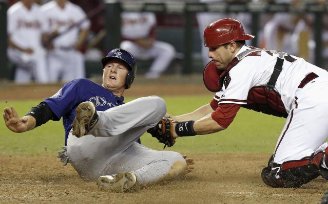 Arizona Diamondbacks' Miguel Montero, right, tags out Colorado Rockies' DJ LeMahieu at home plate in the seventh inning of a baseball game on Friday, Sept. 13, 2013, in Phoenix. (AP Photo/Ross D. Franklin)