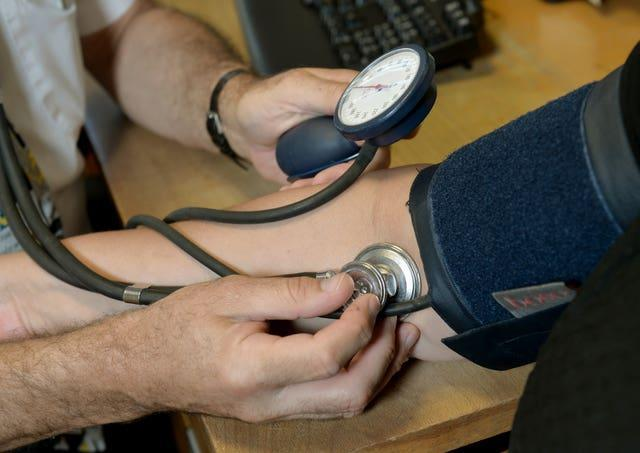 A GP checking a patient's blood pressure (Anthony Devlin/PA)