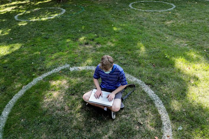 Logan Armstrong, a Cincinnati junior, works while sitting inside a painted circle on the lawn of the Oval during the first day of fall classes on at Ohio State University