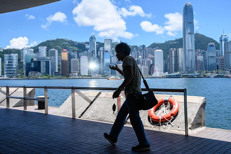 An angler carries a fish on a hook as he walks along a promenade on the Kowloon side of Victoria Harbour, which faces the skyline of Hong Kong Island, in Hong Kong on July 13, 2020. (Photo by Anthony WALLACE / AFP) (Photo by ANTHONY WALLACE/AFP via Getty Images)