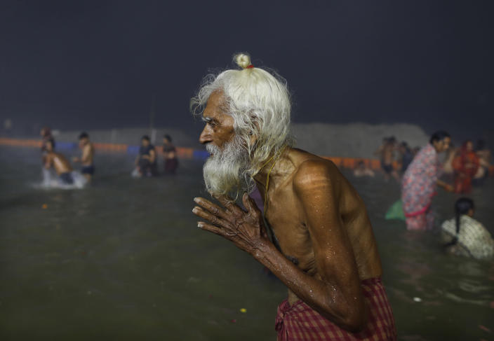 An elderly pilgrim prays after a holy dip at the Sangam in Prayagraj, India, Thursday, Feb. 11, 2021. When the coronavirus pandemic took hold in India, there were fears it would sink the fragile health system of the world's second-most populous country. Infections climbed dramatically for months and at one point India looked like it might overtake the United States as the country with the highest case toll. But infections began to plummet in September, and experts aren't sure why. (AP Photo/Rajesh Kumar Singh)