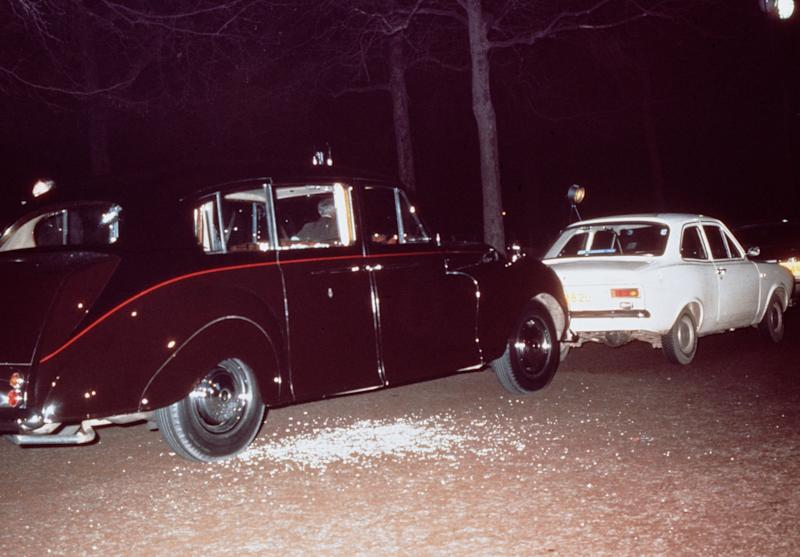 A photo of the aftermath of Ian Ball's attempt to kidnap Princess Anne showing Ball's white Ford Escort parked blocking the path of the Princess's Rolls Royce limousine.