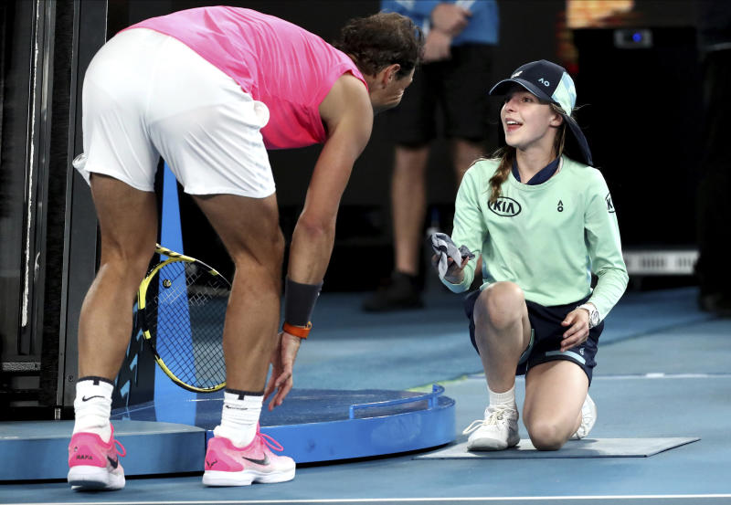 Spain's Rafael Nadal hands a ball girl his bandana after a ball hit her during his second round match against Federico Delbonis of Argentina at the Australian Open tennis championship in Melbourne, Australia, Thursday, Jan. 23, 2020. (AP Photo/Dita Alangkara)