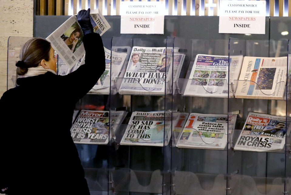 A customer takes a copy of a newspaper headlining Prince Harry and Meghan's explosive TV interview at a newspaper stand outside a shop in London, Tuesday, March 9, 2021. Britain's royal family is absorbing the tremors from a sensational television interview by Prince Harry and the Duchess of Sussex, in which the couple said they encountered racist attitudes and a lack of support that drove Meghan to thoughts of suicide. (AP Photo/Frank Augstein)