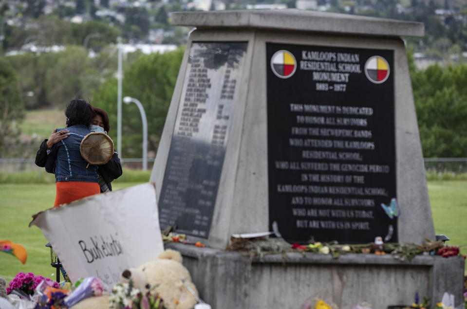 Two women embrace at a monument outside the former Kamloops Indian Residential School where flowers, cards and stuffed animals have been left as part of a growing makeshift memorial to honor the 215 children whose remains have been discovered buried near the facility, Friday, June 4, 2021 in Kamloops, British Columbia. (Darryl Dyck/The Canadian Press via AP)