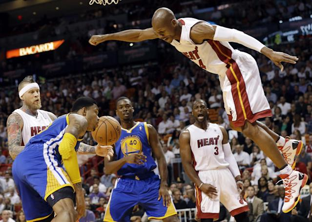 Miami Heat's Ray Allen, right, is fouled after shooting a basket during the first half of an NBA basketball game against the Golden State Warriors, Thursday, Jan. 2, 2014, in Miami. Also shown are Golden State Warriors' Kent Bazemore, left, and Harrison Barnes (40) and Heat's Dwyane Wade (3). (AP Photo/Lynne Sladky)