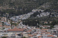 This shows the port city of Vathy and the refugee and migrant camp, top, in the eastern Aegean island of Samos, Greece, on Friday, June 11, 2021. An inflatable dinghy carrying nearly three dozen people reached the Greek island of Samos from the nearby Turkish coast. Within 24 hours, refugee rights groups say, the same group was seen drifting in a life raft back to Turkey. But of the 32 people determined to have initially made it to Samos, only 28 were in the raft the Turkish coast guard retrieved at sea. Days later, the missing four, a Palestinian woman and her three children, appeared in Samos' main town, apparently having eluded authorities. (AP Photo/Petros Giannakouris)