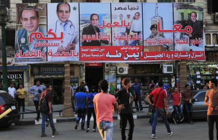 People walk under an election campaign billboard of presidential candidate and former army chief Abdel Fattah al-Sisi a day ahead of presidential elections at Talaat Harab Square in Cairo