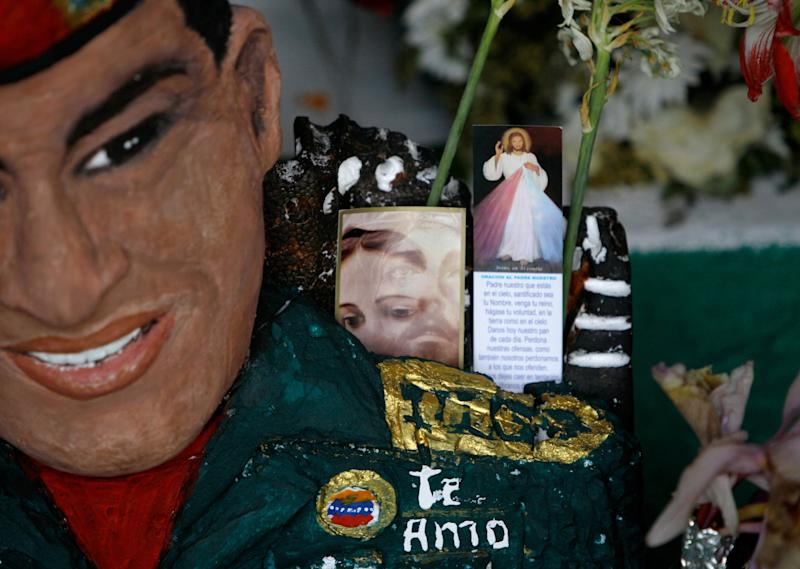 "A bust of late Venezuela's President Hugo Chavez is adorned with flowers and religious images inside a people's shrine built in his honor at the ""23 de Enero"" or ""23rd of January"" slum in Caracas, Venezuela, Wednesday, April 3, 2013. The shrine, named ìSaint Hugo Chavez del 23î, has been visited by tens of thousands of Venezuelans to pay homage to a president for some, a saint for others. (AP Photo/Fernando Llano)"