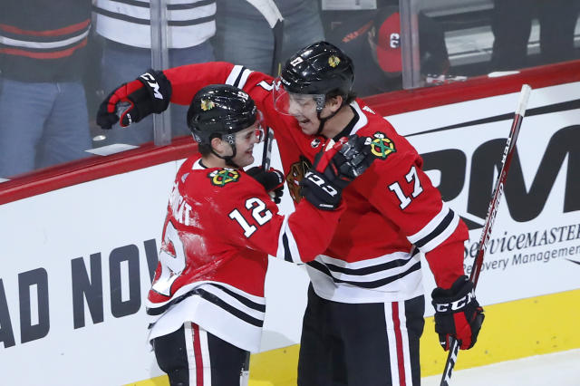 Chicago Blackhawks' Alex DeBrincat (12) and Dylan Strome celebrate DeBrincat's goal during the first period of an NHL hockey game against the Vancouver Canucks, Thursday, Nov. 7, 2019, in Chicago. (AP Photo/Charles Rex Arbogast)
