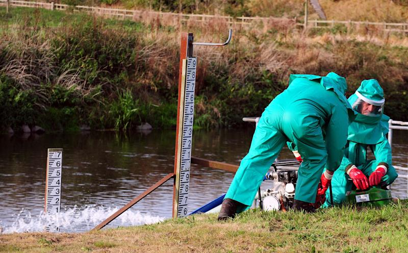 Environment Agency workers treat the River Trent at Yoxhall, Staffordshire, after it was contaminated with untreated sewage and cyanide.