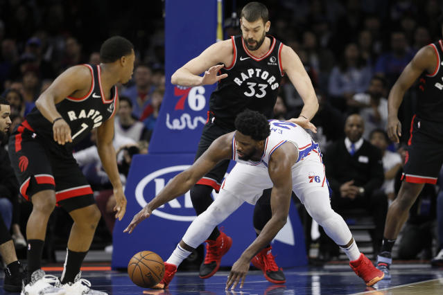 Philadelphia 76ers' Joel Embiid (21) reaches for a loose ball as Toronto Raptors' Marc Gasol (33) and Kyle Lowry (7) look on during the first half of an NBA basketball game, Sunday, Dec. 8, 2019, in Philadelphia. (AP Photo/Matt Slocum)